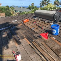 Removing shingles and fixing  a leak under the solar hot water panels