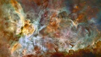 In celebration of the 17th anniversary of the launch and deployment of NASA's Hubble Space Telescope, a team of astronomers is releasing one of the largest panoramic images ever taken with Hubble's cameras. It is a 50-light-year-wide view of the central region of the Carina Nebula where a maelstrom of star birth - and death - is taking place. Hubble's view of the nebula shows star birth in a new level of detail. The fantasy-like landscape of the nebula is sculpted by the action of outflowing winds and scorching ultraviolet radiation from the monster stars that inhabit this inferno. In the process, these stars are shredding the surrounding material that is the last vestige of the giant cloud from which the stars were born. The immense nebula contains at least a dozen brilliant stars that are roughly estimated to be at least 50 to 100 times the mass of our Sun. The most unique and opulent inhabitant is the star Eta Carinae, at far left. Eta Carinae is in the final stages of its brief and eruptive lifespan, as evidenced by two billowing lobes of gas and dust that presage its upcoming explosion as a titanic supernova. The fireworks in the Carina region started three million years ago when the nebula's first generation of newborn stars condensed and ignited in the middle of a huge cloud of cold molecular hydrogen. Radiation from these stars carved out an expanding bubble of hot gas. The island-like clumps of dark clouds scattered across the nebula are nodules of dust and gas that are resisting being eaten away by photoionization. The hurricane blast of stellar winds and blistering ultraviolet radiation within the cavity is now compressing the surrounding walls of cold hydrogen. This is triggering a second stage of new star formation. Our Sun and our solar system may have been born inside such a cosmic crucible 4.6 billion years ago. In looking at the Carina Nebula we are seeing the genesis of star making as it commonly occurs along the dense spiral