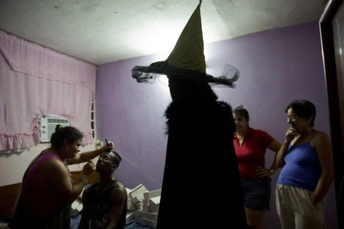 Marilyn Alvarez puts makeup on her daughter's friend as they prepare for a Halloween party in Havana, Cuba, Friday, Oct. 28, 2016. Cubans are immersed in U.S. popular culture and, increasingly, U.S. products brought by expatriates visiting family on the island. (AP Photo/Ramon Espinosa)