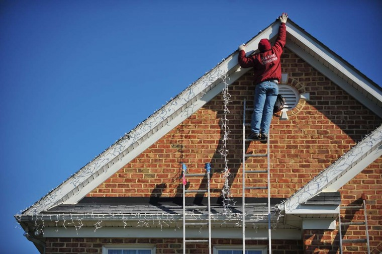 """Roberto Morales from the Frederick, Md, company """"The King of Christmas"""", hangs a string of icicle lights at the top of the roof line on a home located in Timonium. (Gene Sweeney Jr./Baltimore Sun)"""