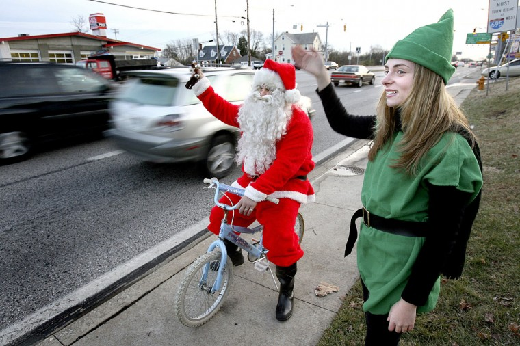 Jim Stavropoulos as Santa Claus and his elfin assistant Amber Stevens try to encourage passsing motorists to stop for the free toy giveaway at St. Peter's Lutheran Church Friday afternoon. The 'Friends of Jim Stavropoulos Outreach Center' at the church held a Santa visit combined with a toy giveaway on December 17, 2005. (Francis Gardler/Patuxent Publishing)