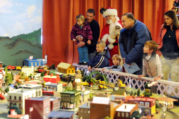 Santa Claus stands amongst several families as they all check out the Fire Museum of Maryland's holiday train garden in Lutherville on Saturday, November 24, 2012. The new O-scale train garden is based off a 1950's theme and features various iconic Baltimore-area structures. (Brian Krista/Patuxent Publishing)