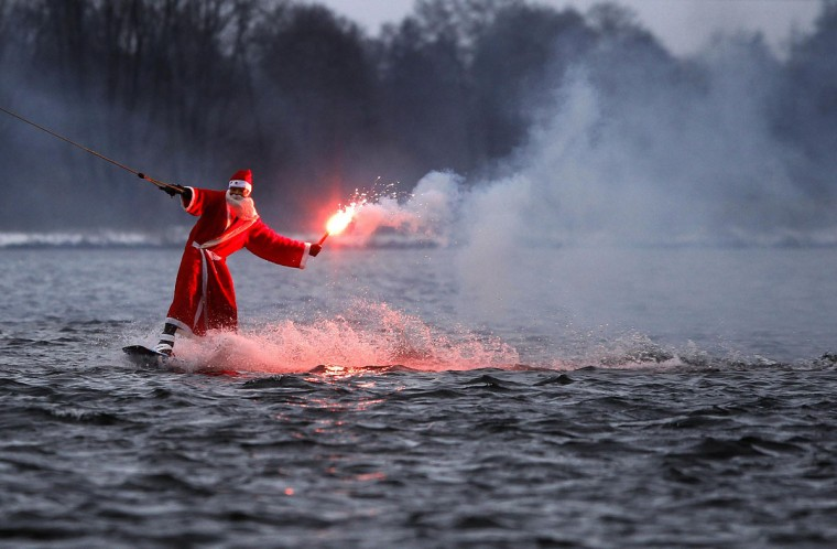 A man dressed as Santa Claus holds a flare as he wakeboards at a water ski set on a small lake in Hamburg December 5, 2010. (Christian Charisius/Reuters)