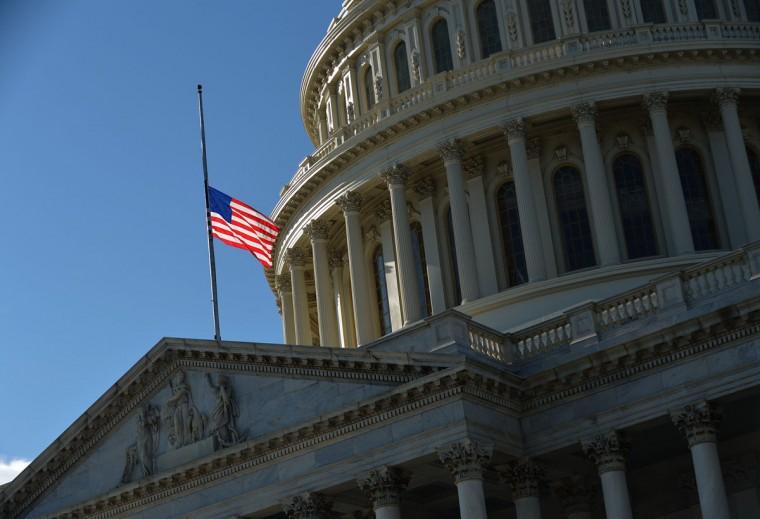 Флаг США летит на половине сотрудников выше Капитолия США в Вашингтоне, округ Колумбия, чтобы оплакивать жертв Sandy Hook Элементарные съемки школа в Ньютаун, штат Коннектикут (Mandel Ngan / AFP / Getty Images)
