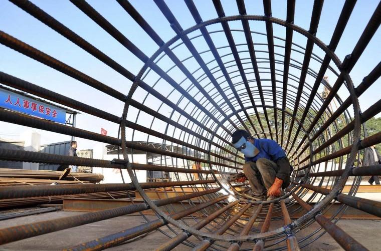Рабочий сваривает стальной арматуры на строительной площадке для нового железнодорожного вокзала в городе Нинбо, провинция Чжэцзян.  Ежегодный рост на заводе производство в Китае, инвестиционных и розничных продаж, возможно, получил в благодарность темпами с ноября по последнее стимулирования экономического роста политика, Reuters опрос показал, что снижает шансы на дальнейшую поддержку политики, как инфляция поднимает.  (China Daily / Reuters помощью)