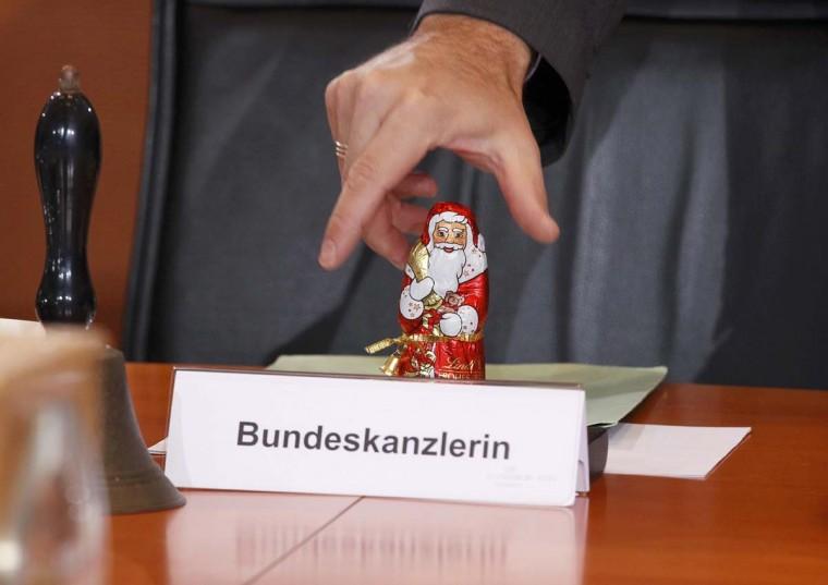 Шоколад Санта-Клаус, по случаю Дня Святого Николая, стоит на столе за имя карты место для канцлера Германии Ангелы Меркель перед еженедельные заседания кабинета министров в Берлине.  (Wolfgang Rattay / Reuters фото)