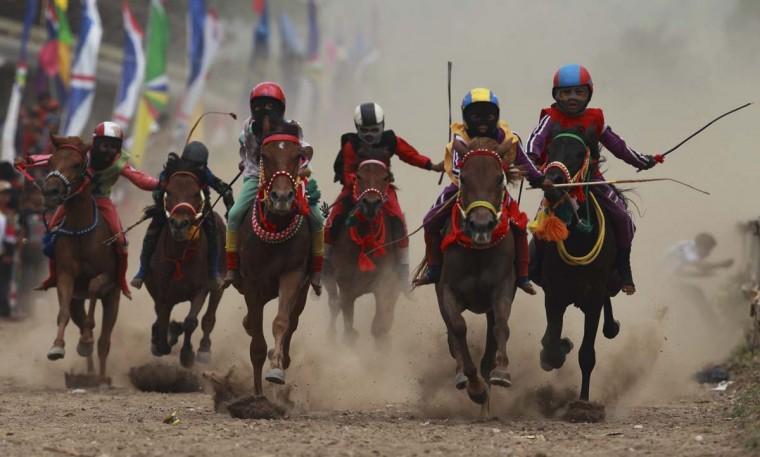 Ребенка жокеев гонки лошадей на ипподроме за пределами Бима.  Десятки ребенка жокеев, некоторые в возрасте восьми-летний принять участие в гонках.  Фото сделано 17 ноября 2012.  (Beawiharta / Reuters)