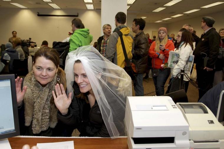 Джери Эндрюс (L), 43, и Эми Эндрюс, 33, клятву, что документы для их свидетельство о браке является точной в Сиэтле, штат Вашингтон.  Закон, разрешающий однополые брак вступило в силу в штате Вашингтон в четверг, и чиновники подготовлены к потоку брака заявок на получение лицензий от геев и лесбиянок стремятся обмен клятвами.  Вашингтон вошел в историю в прошлом месяце, как одном из трех состояний США, где браки права были распространены на однополые пары путем всенародного голосования, присоединившись Мэриленд и Мэн попутно инициативы голосования признания гей-свадьбы.  (Marcus Доннер / Reuters фото)