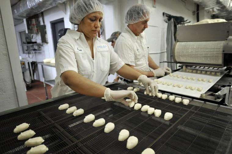 Бланка Гомес дает в форме яйца ванили, сливочного крема номер на поясе, как Майкл Ветцель работает экструдера. Скоро будет шоколад облачили яйца будут использоваться в Мэри Сью Конфеты Банни BonanZoo в мерилендском Зоопарк в Балтиморе. (Ким Hairston/Baltimore Sun)