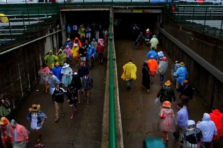 Гонка болельщики проходят через туннель, укрываясь от дождя до 139-й ход дерби в Кентукки на ипподроме Черчилль 4 мая 2013 года в Луисвилле, штат Кентукки.  (Doug Pensinger / Getty Images)