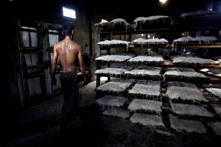 Ми летек сидит на стойках перед процесс пропаривания на Ми летек Srandakan завод в деревне, Bantul 22 мая 2013 года в Джокьякарта, Индонезия. Ясир Feri Ismatrada взял на себя семейный бизнес производства Ми летек основанной его покойный дед. Одну тонну каменного цилиндр поворачивается на коров, чтобы молоть муку, технику редко можно увидеть сегодня. Ясир ставит большое значение на справедливое отношение к своим 40 сотрудникам управления прибыли ограничен на уровне 10%, приоритетности интересов персонала. Ми летек продаются за 8000 рупий или $ 80 центов за килограмм. (Ulet Ifansasti / Getty Images)