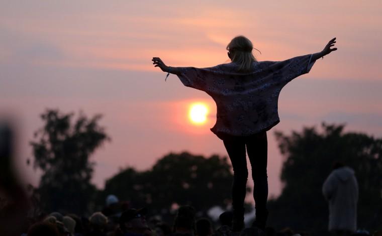 Женщина стоит на скале в каменный круг, как люди собираются на закат на фестивале Гластонбери современного исполнительского искусства сайт на достойном Farm, Pilton на 26 июня 2013 близ Гластонбери, Англия.  (Matt Cardy / Getty Images)
