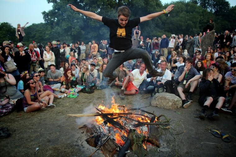 Человек прыгает через огонь, который был зажжен внутри каменного круга, как люди собираются на закат на фестивале Гластонбери современного исполнительского искусства сайт на достойном Farm, Pilton на 26 июня 2013 возле Гластонбери, Англия.  (Matt Cardy / Getty Images)