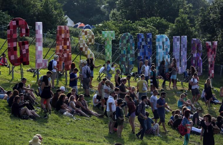 Люди сидят в ВС ниже Гластонбери знак на фестивале Гластонбери современного исполнительского искусства сайт на достойном Farm, Pilton на 26 июня 2013 возле Гластонбери, Англия.  (Matt Cardy / Getty Images)