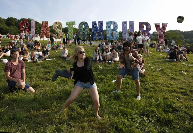 Фестиваль любителей играть в бейсбол, ватин пивную банку с загрузочным Веллингтоне, в первый день музыкального фестиваля Гластонбери на достойном Ферма в Сомерсете 27 июня 2013 года.  (Olivia Harris / Reuters)