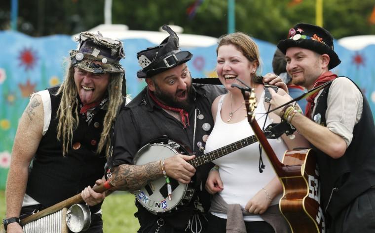 Фестиваль посетитель (2-е R) позирует для фото с фольклорным ансамблем на третий день музыкального фестиваля Гластонбери на достойном Ферма в Сомерсете, 28 июня 2013 года.  (Olivia Harris / Reuters)