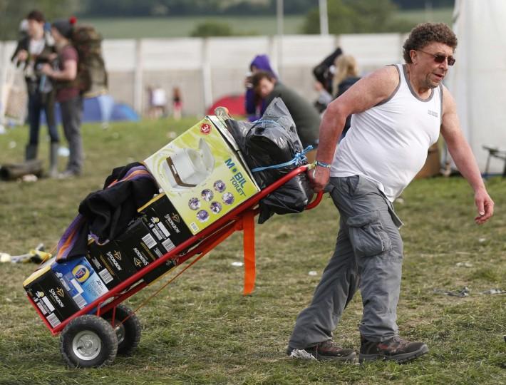 Фестиваль посетитель колесами в мобильный туалет и ящики с пивом, как он прибыл в лагерь на второй день музыкального фестиваля Гластонбери на достойном Ферма в Сомерсете, 27 июня 2013 года.  (Olivia Harris / Reuters)