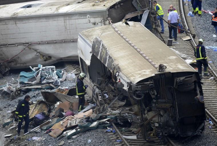 Спасатели проверяет автомобиль поезда на месте аварии поезда в районе города Сантьяго-де-Компостела 25 июля 2013 года.  Поезд мчался с рельсов 24 июля 2013 года в северо-западе Испании погибли по меньшей мере 77 пассажиров и ранив более 140, сказал чиновник сегодня, смертоносных железнодорожная катастрофа в стране более 40 лет.  (Мигель Riopa / Getty Images)