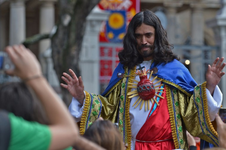 A man dressed as Jesus Christ is seen among the crowd gathering outside the San Joaquin Episcopal Palace in Rio de Janeiro, Brazil, before Pope Francis delivered the Angelus prayer on July 26, 2013. (Gabriel Bouys/AFP/Getty Images)