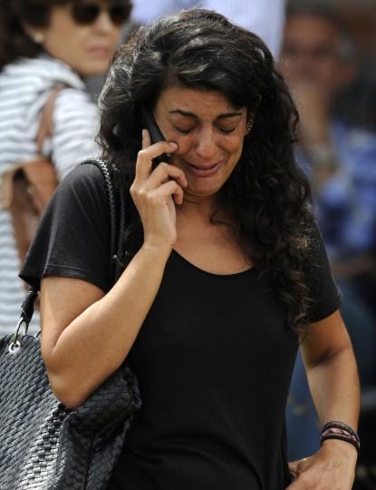 Родственник одной из жертв железнодорожной катастрофы плачет, как она говорит по телефону в Сантьяго-де-Компостела, северо-западе Испании, 25 июля 2013 года.  Поезд сошел с рельсов за пределами древних северо-западной испанском городе Сантьяго-де-Компостела в среду вечером, погибли по меньшей мере 78 человек и ранено до 131 в одном из худших бедствий Европы железной дороге.  (Eloy Alonso / Reuters фото)