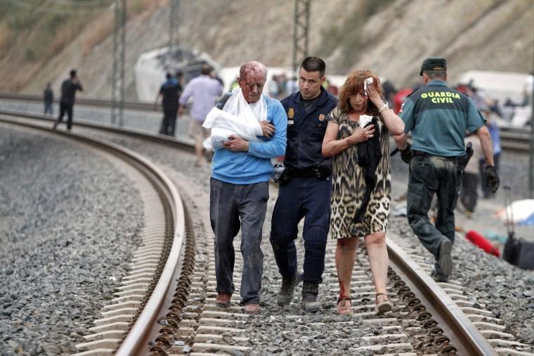 Жертвы помогали спасателям после поезда разбился под Сантьяго-де-Компостела, северо-западе Испании 24 июля 2013 года.  По меньшей мере 56 человек погибли после того, как поезд сошел с рельсов на окраине северном испанском городе Сантьяго-де-Компостела, глава Галиция регионе Испании, Альберто Нуньес Feijoo, сообщил телевидению Галисии.  (Моника Ferreiros / Ла Вос де Галиция / через Reuters)
