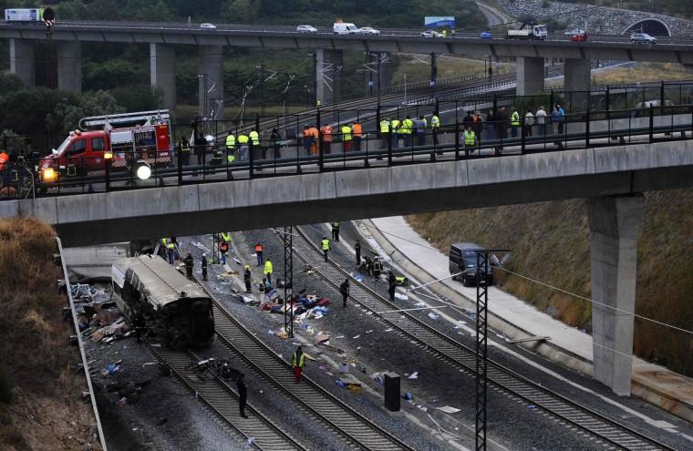 Спасатели стою среди обломков крушения поезда близ Сантьяго-де-Компостела, северо-западе Испании, 25 июля 2013 года.  Поезд сошел с рельсов за пределами древних северо-западной испанском городе Сантьяго-де-Компостела в среду вечером, погибли по меньшей мере 77 человек и ранено до 131 в одном из худших бедствий Европы железной дороге.  (Eloy Alonso / Reuters фото)