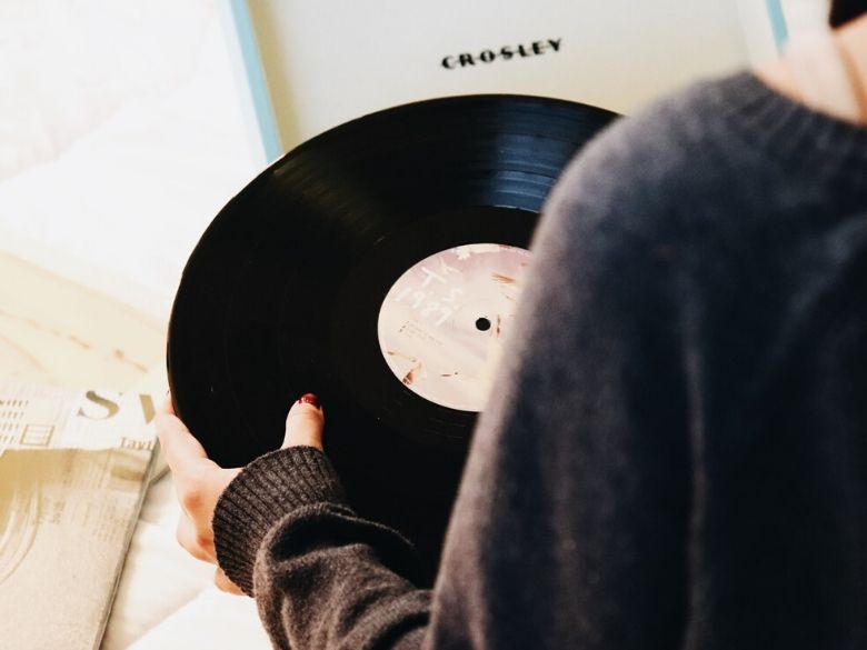 over shoulder of woman holding a warped record in her hands