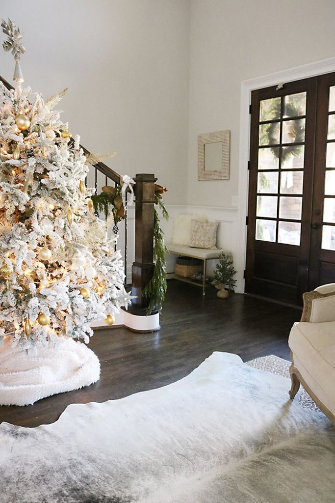 christmas-house-decorations-tips, winter white christmas, flocked white tree, entry christmas decorations, cow hide rug, magnolia garland, southern christmas christmas-decorations-living-room-shot, fireplace mantle christmas decorations, magnolia garland, winter white christmas, living room christmas decorations