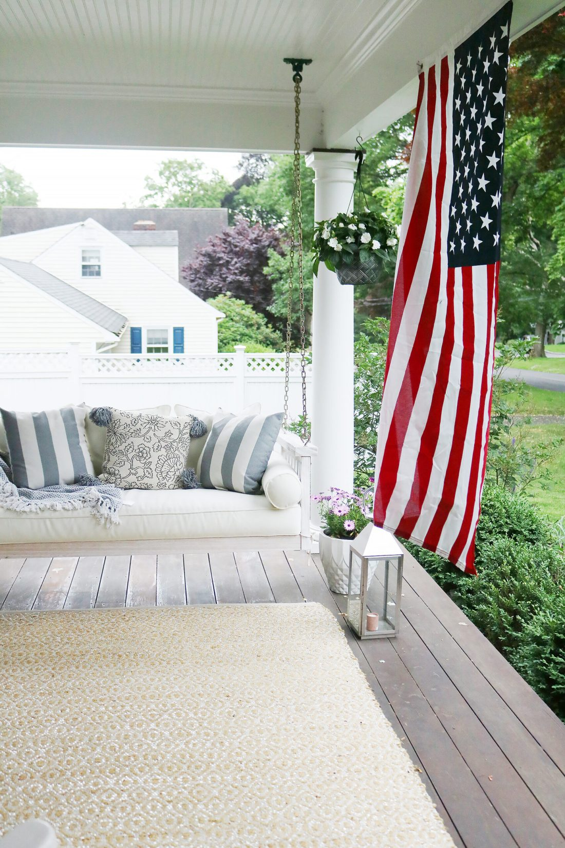 A beautiful home exterior can make or break curb appeal! Sharing 7 easy and simple curb appeal ideas. American flag by porch swing || Darling Darleen Top CT Lifestyle Blogger home exterior | outdoor charm | curb appeal ideas | home exterior ideas | white house with gray shutters | porch swing | shutter | new england charm | blue front door | #darlingdarleen