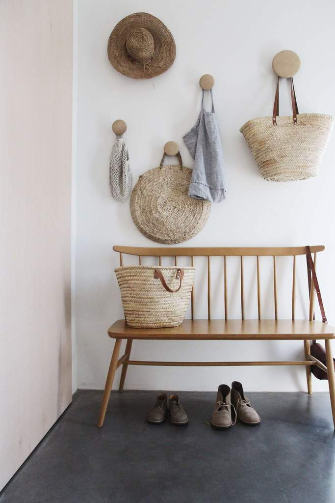 A bench with hooks hung on the wall with straw bags