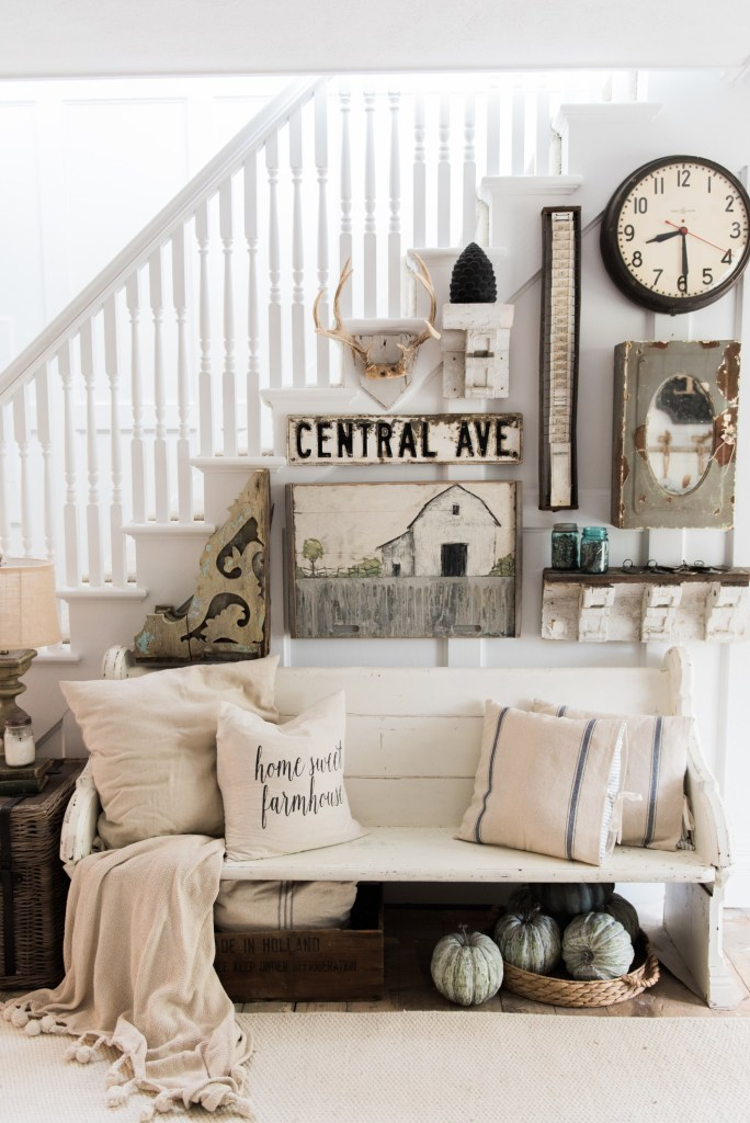 White upholstered bench in an entryway with farmhouse decor