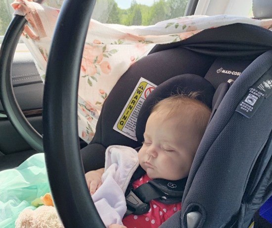 A photo of a baby asleep in a car seat