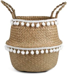 A Woven Seagrass Belly Basket with white pompom trim and 2 handles