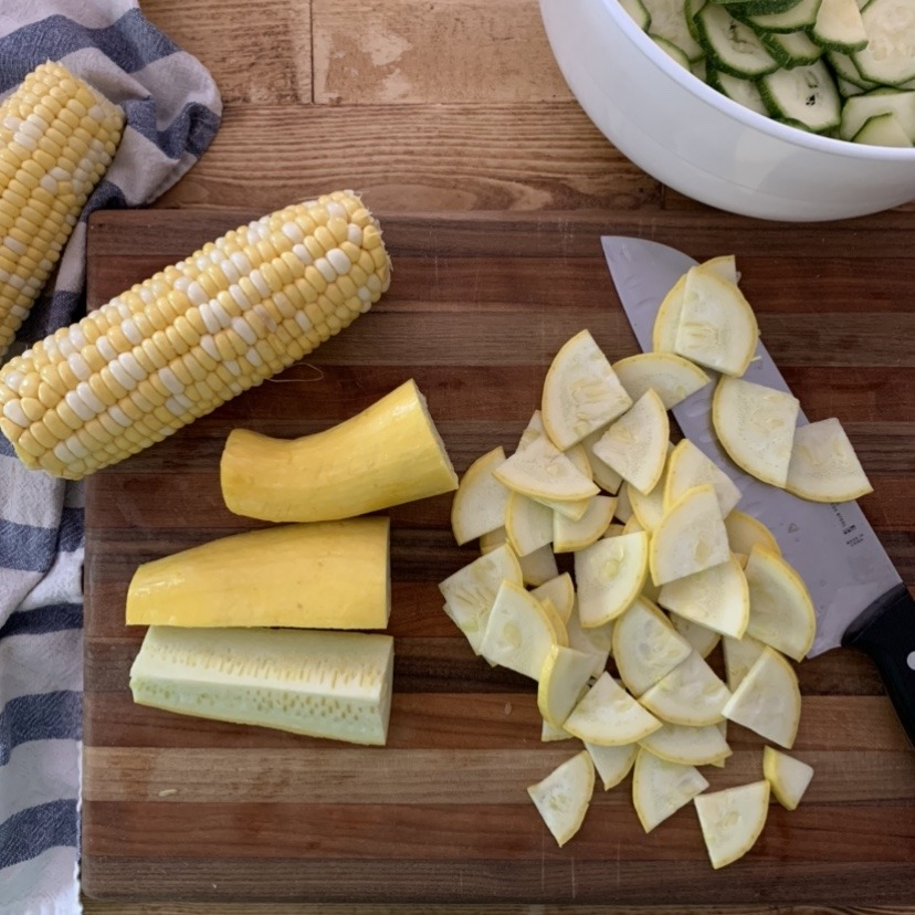 A wooden cutting board with fresh squash, corn on the cob, and sliced zucchini.