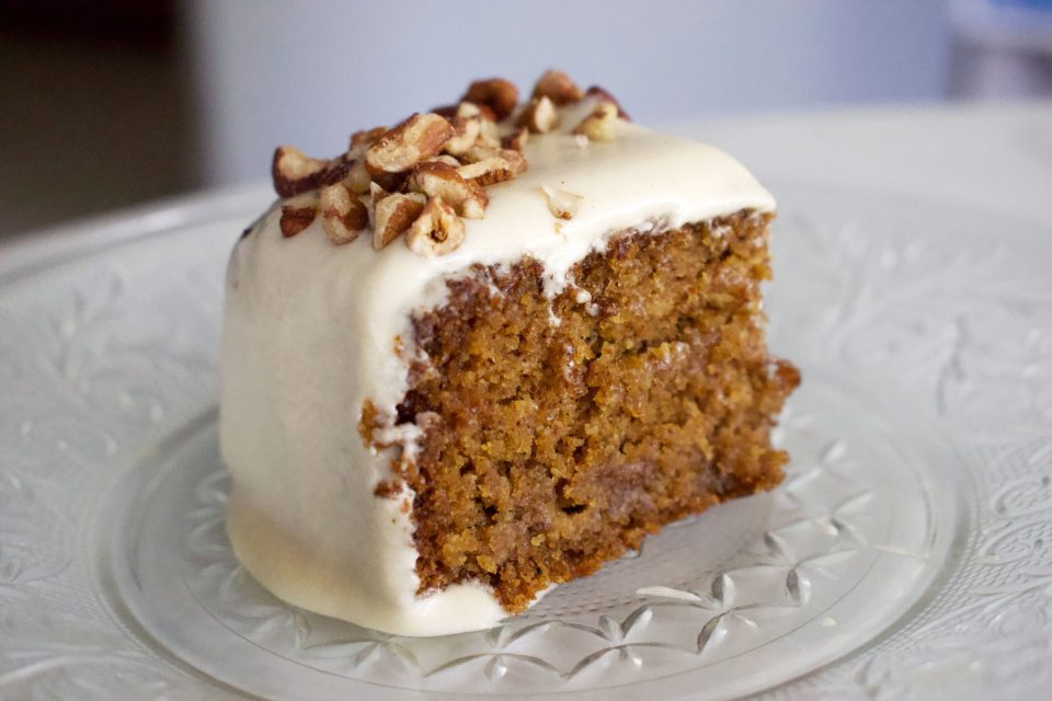 A slice of cake with cream cheese frosting and a border of chopped pecans sits on top of a crystal plate.