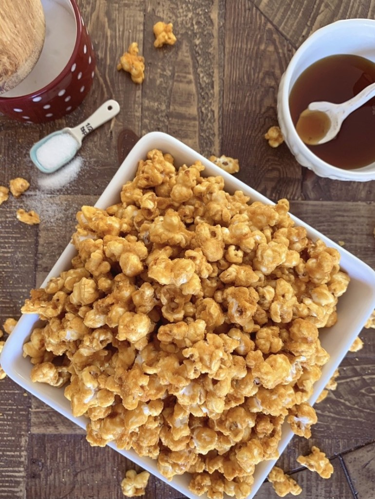 A bowl overflowing with homemade caramel corn and a smaller bowl of maple syrup next to it.