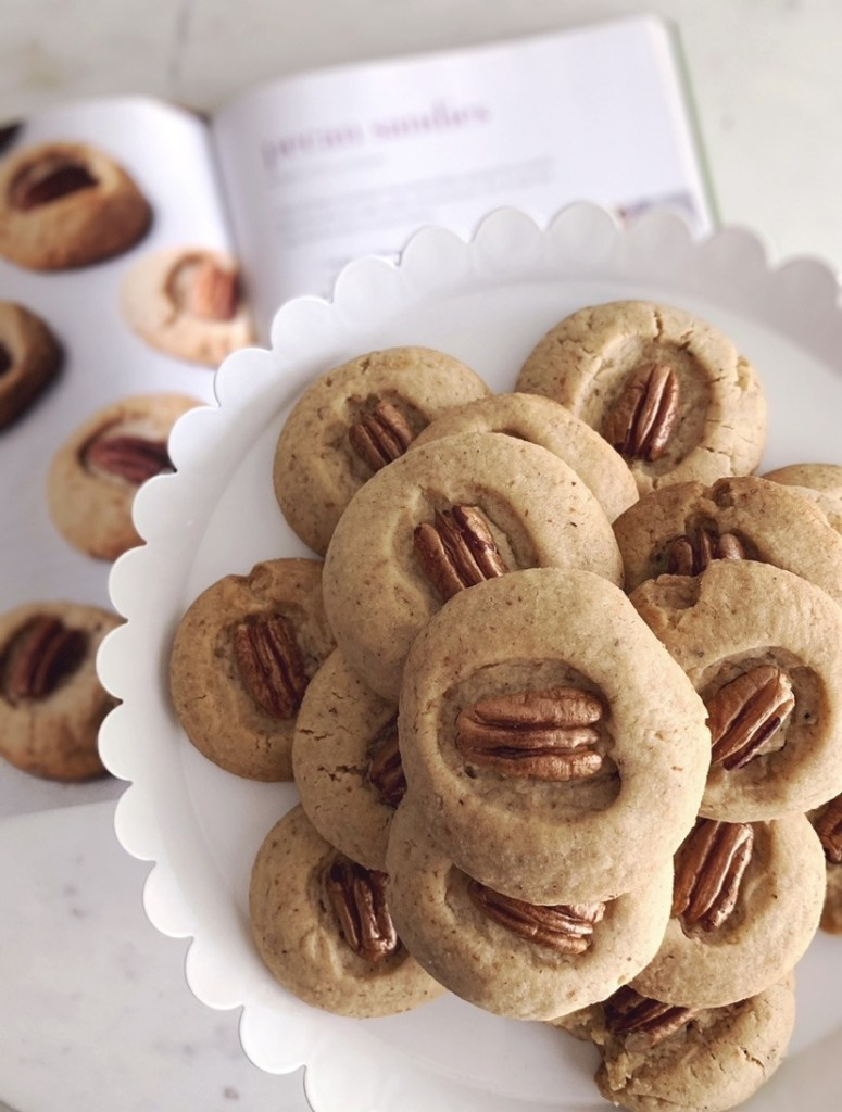 Pecan Sandies on a cake stand with the recipe in the background.