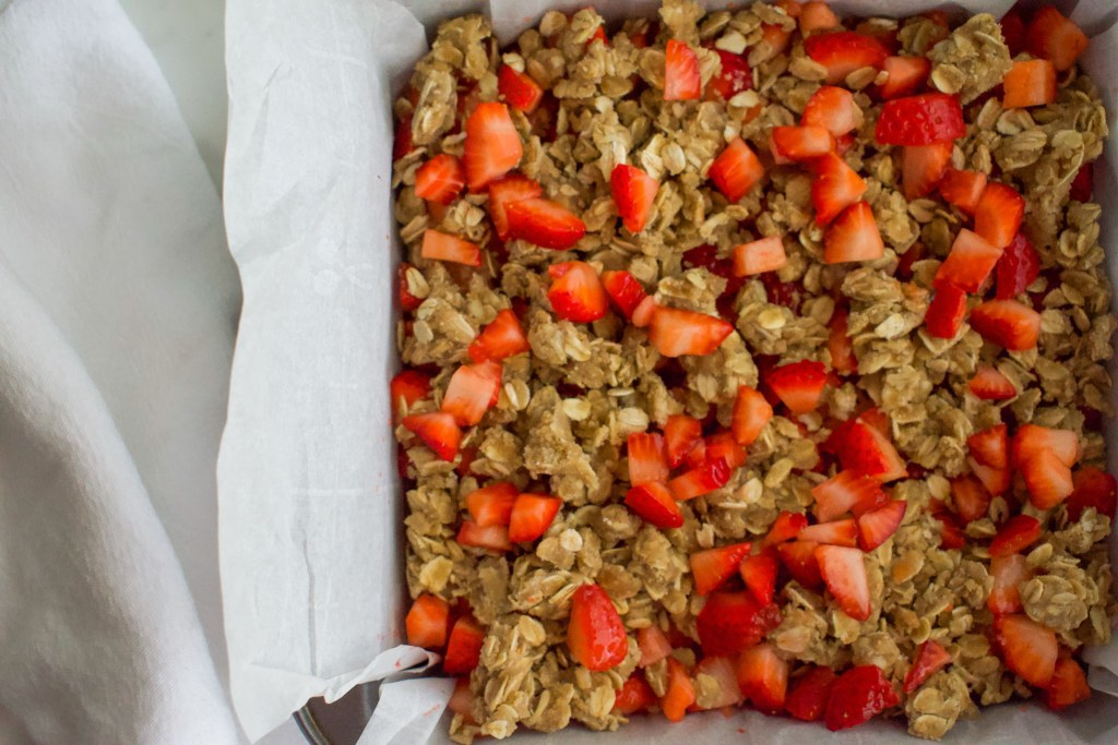 A baking pan of strawberry crumble bars with chopped strawberries sprinkled over the top.