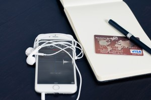 iphone, visa card, and notepad on black desk