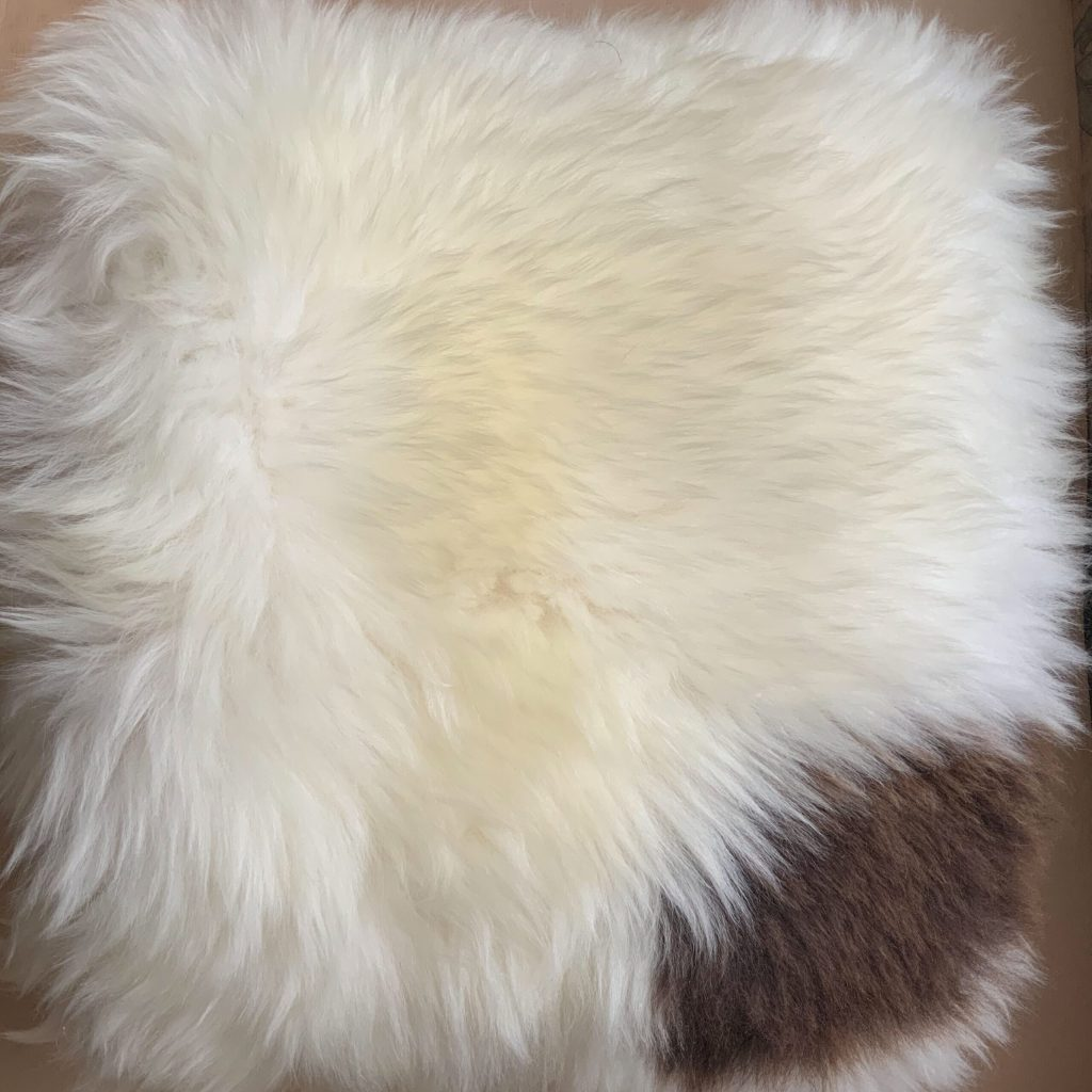 sheepskin folded into square with large brown spot in bottom right