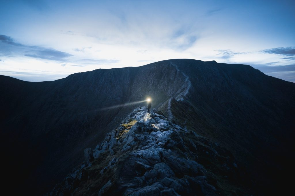 person with head torch on mountain