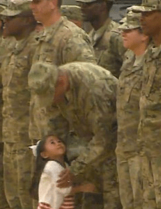 Little Karas Ogelsby looks up with love at her daddy, just home from nine months in the Middle East.