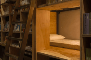 Book lover guest sleep among the bookshelves at Tokyo's Book and Bed Hotel, a library-hotel.