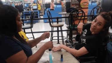 Walmart employee Ebony Harris uses her break to paint the fingernails of a woman with a disability who had been denied a manicure because she was told she moves too much.