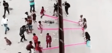 Two American professors install pink plastic seesaws through border fence so children on both sides of border can play together.