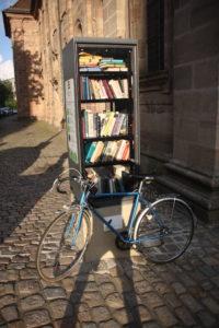 Ein Fahrrad lehnt an einem öffentlichen Bücherschrank