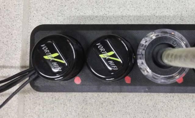 Steckerleiste mit Vortex HiFi Distortion Field Absorber Ableitungskabel links. Über eine Wellenwiderstandsoptimierte Leitung wird auf den inneren Leiter des koaxialen Lautsprecherkabels ein Erdpotential gelegt. Dies verhindert Wirbelströme und eine Abstrahlung von Störungen. Der Stecker links schaft den Kontakt zum Erdpotential.