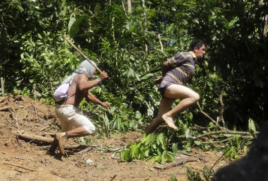 Ένας Ka'apor Ινδιάνος πολεμιστής κυνηγάει έναν υλοτόμο ο οποίος προσπάθησε να δραπετεύσει. Ο υλοτόμος είχε αιχμαλωτιστεί κατά τη διάρκεια μιας αποστολής εκδίωξης από την περιοχή Alto Turiacu, κοντά στην κοινότητα Centro do Guilherme στα βορειοανατολικά της πολιτείας Maranhao της Βραζιλίας στην κοιλάδα του Αμαζονίου, στις 7 Αυγούστου του 2014. Πηγή: www.lifo.gr