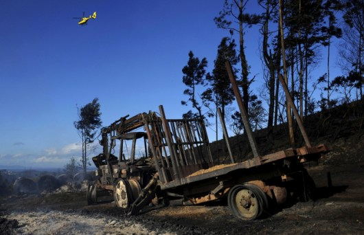 An emergency services helicopter flies over a burnt out area in La Caridad