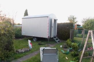 Grauer Bauwagen steht an seinem endgültigen Platz im Garten vor einer Lebensbaumhecke.